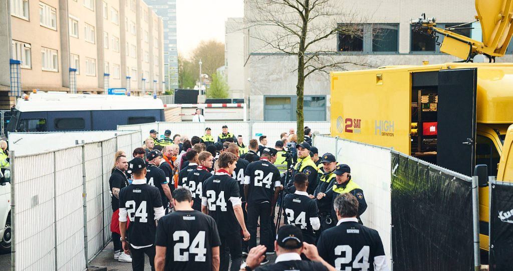 Football team in the middle of police officers during PSV Eindhoven title celebrations