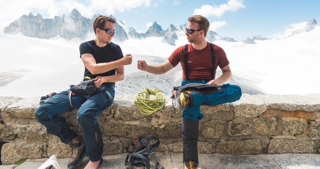 Two alpinists fist-bumping in the Swiss Alps