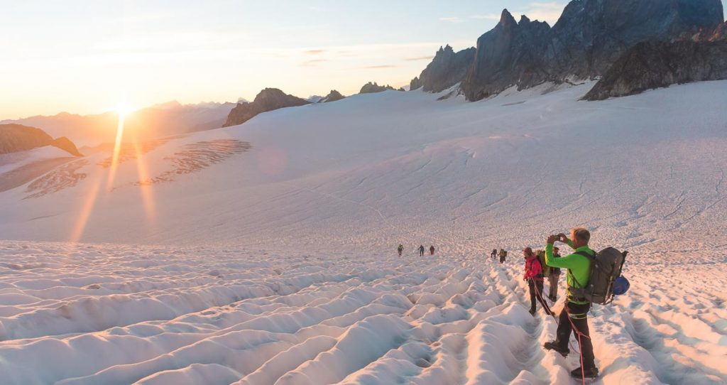 Group of alpinists enjoying a sunrise in the Swiss alps