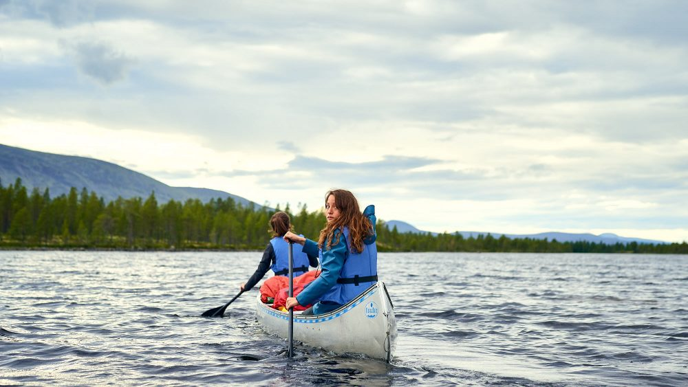 Two girls in a canoe on a lake in Norway