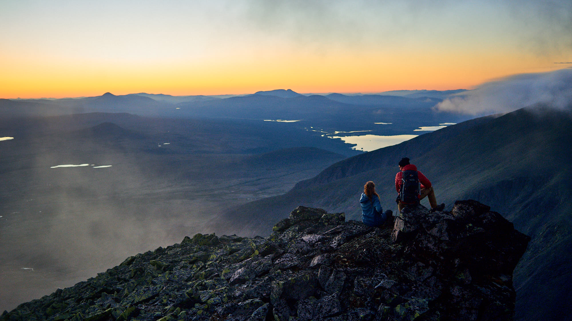 Young couple enjoy the sunset on a mountaintop in Norway