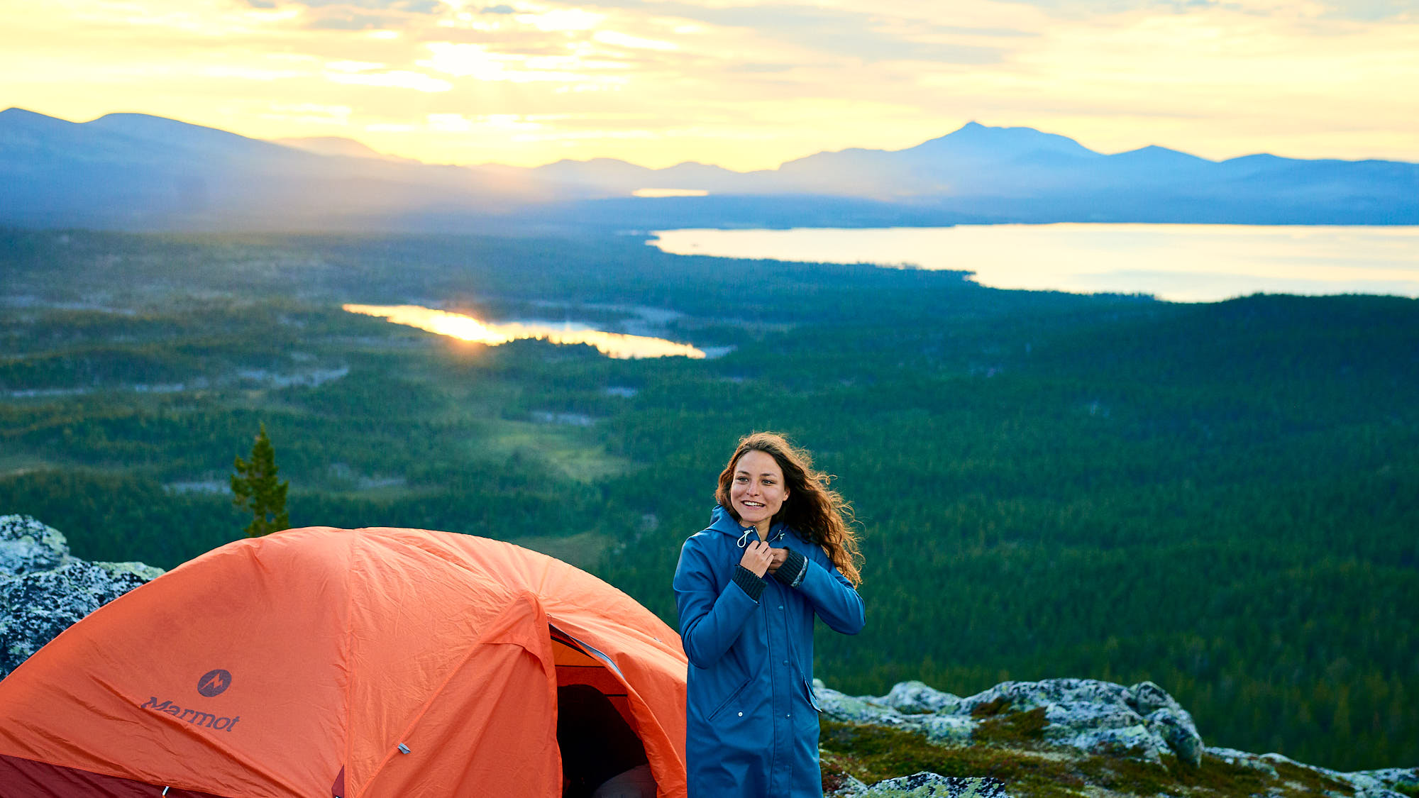 Pretty girl stands by her tent on a hill in Norway