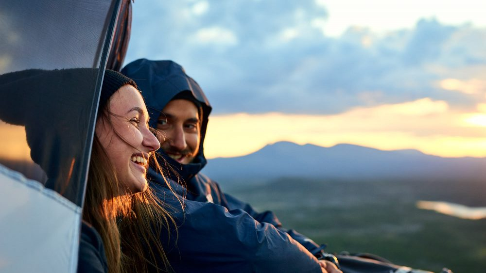 Couple in a tent on a mountain in Norway, with an epic view of the landscape