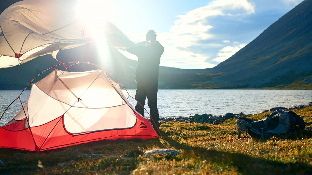Hiker setting up his tent by a mountain lake in Norway