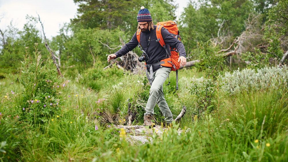 Hiker taking careful steps in a swamp in Norway
