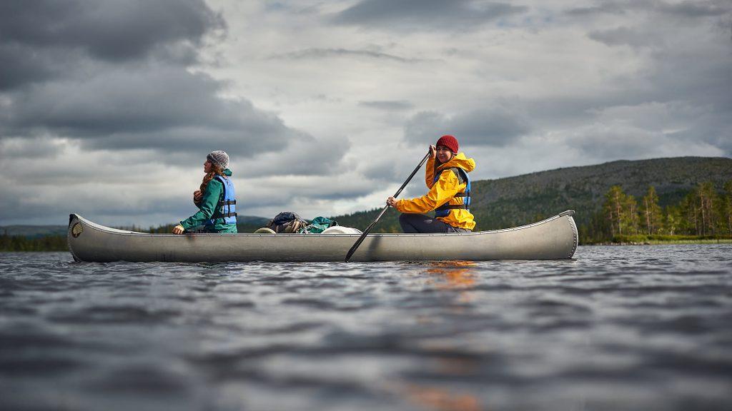 Girl relaxing in a canoe on a Norwegian lake