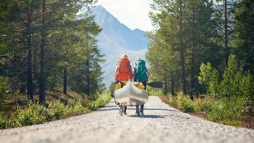 Canoe being pulled on a gravel road in Norway