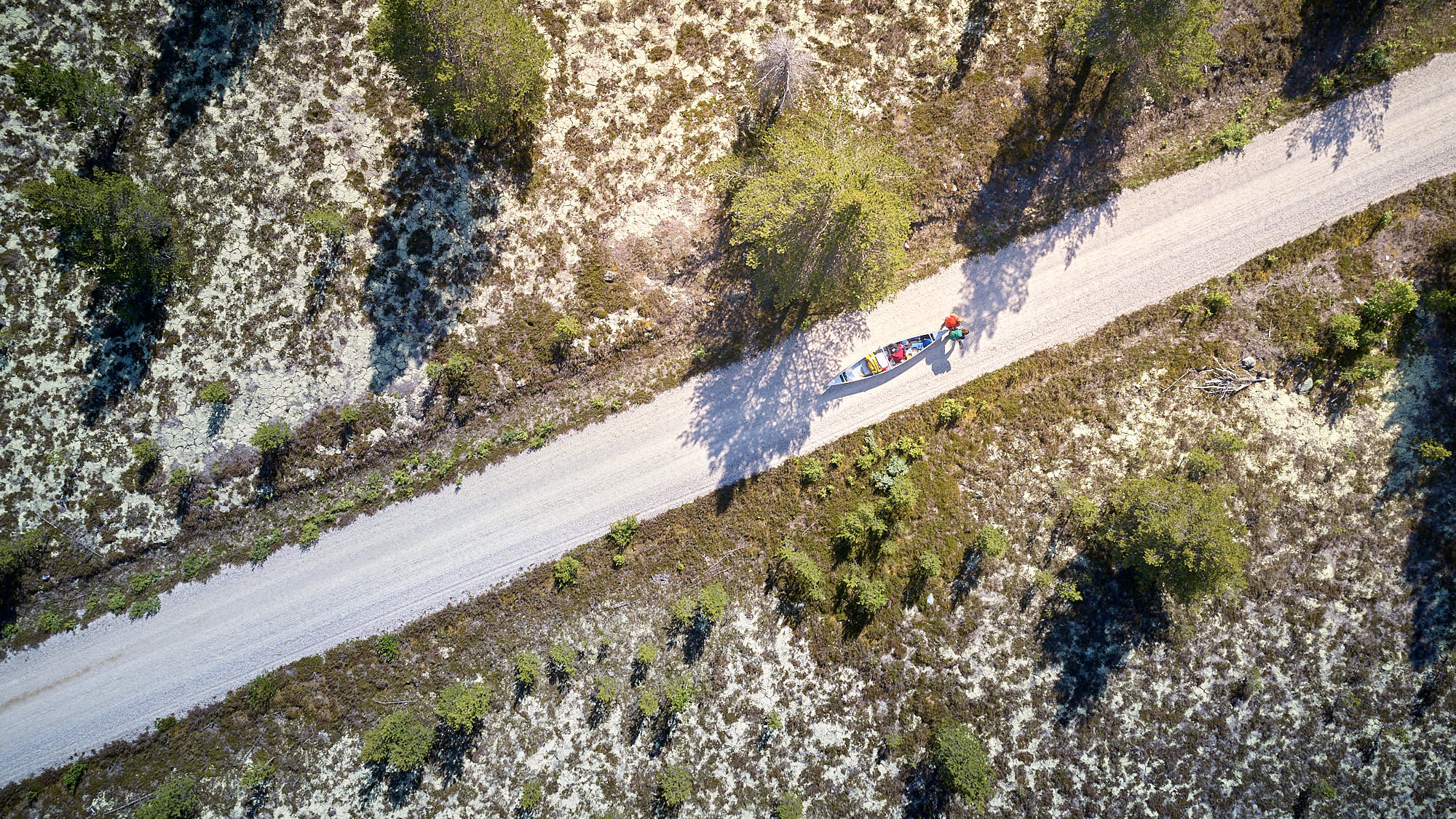 Aerial view of a canoe being pulled on a gravel road in Norway