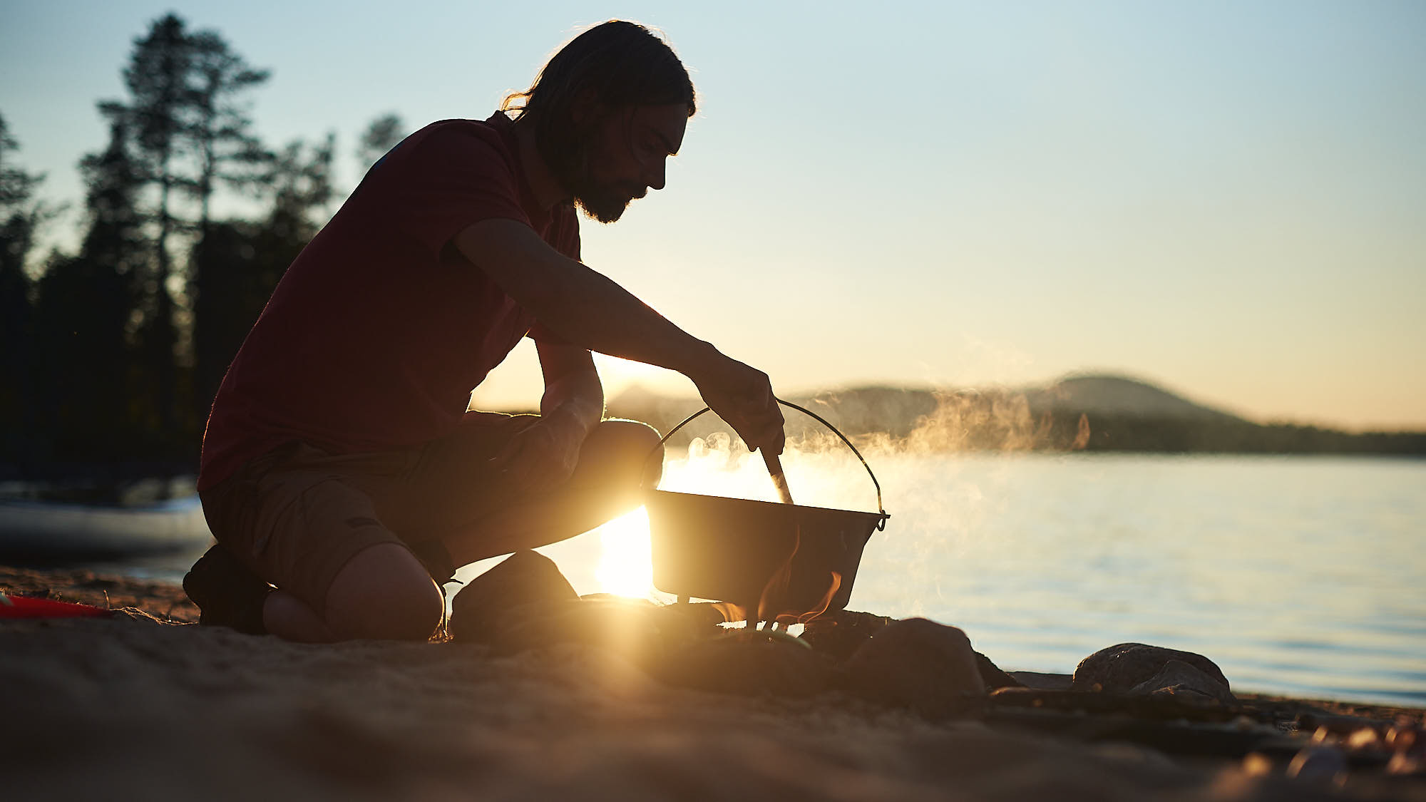 Hiker cooking a meal on a fire in the wild on a beach by a lake in Norway