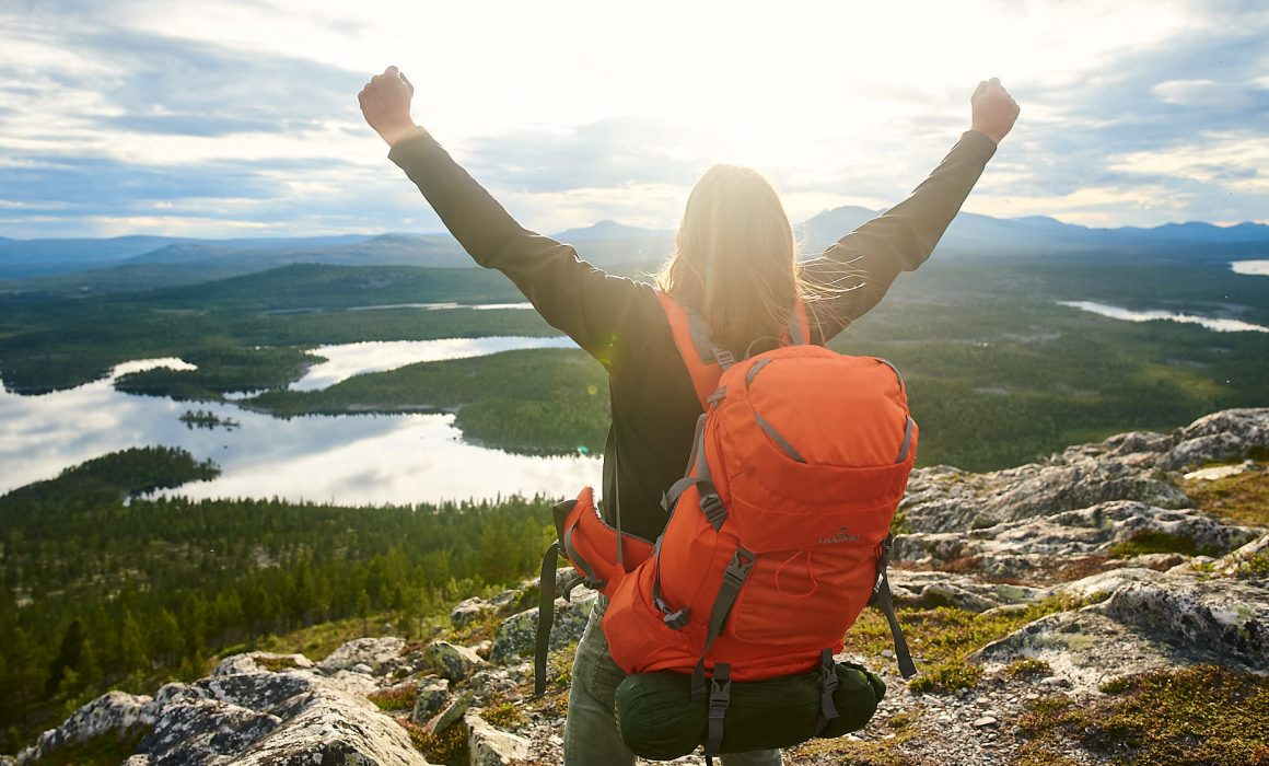 Hiker wearing a backpack on top of a mountain, cheering