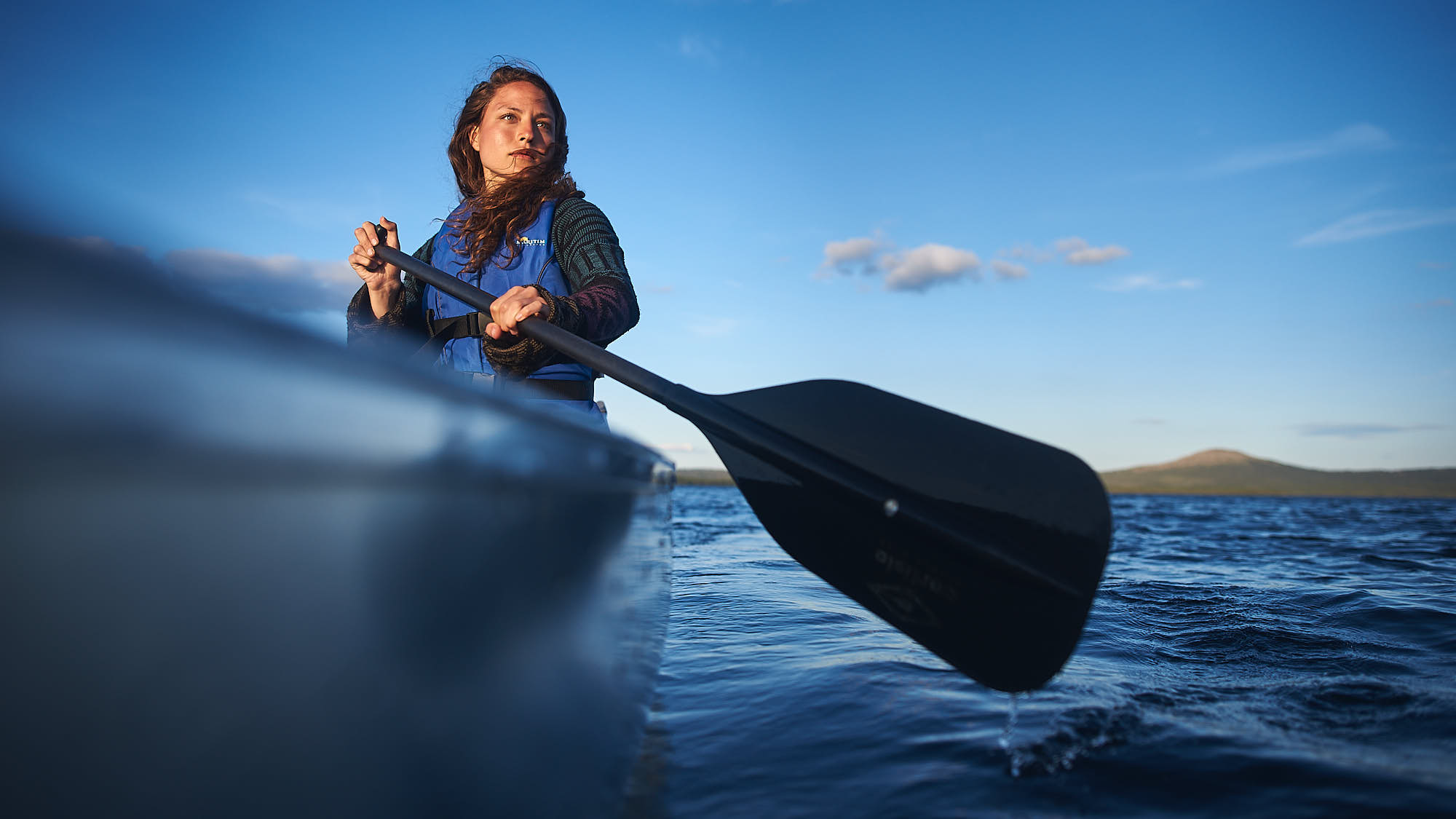 Girl with a paddle in a canoe on a lake in Norway
