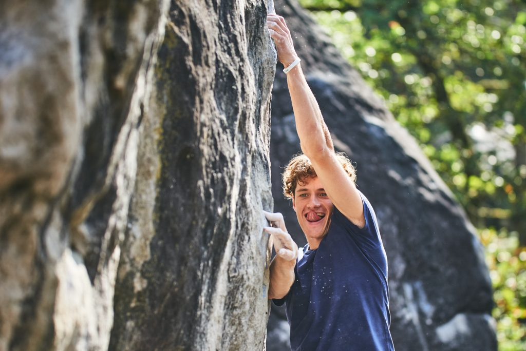 Mad Rock athlete Kipras Baltrunas climbing a boulder problem in Fontainebleau