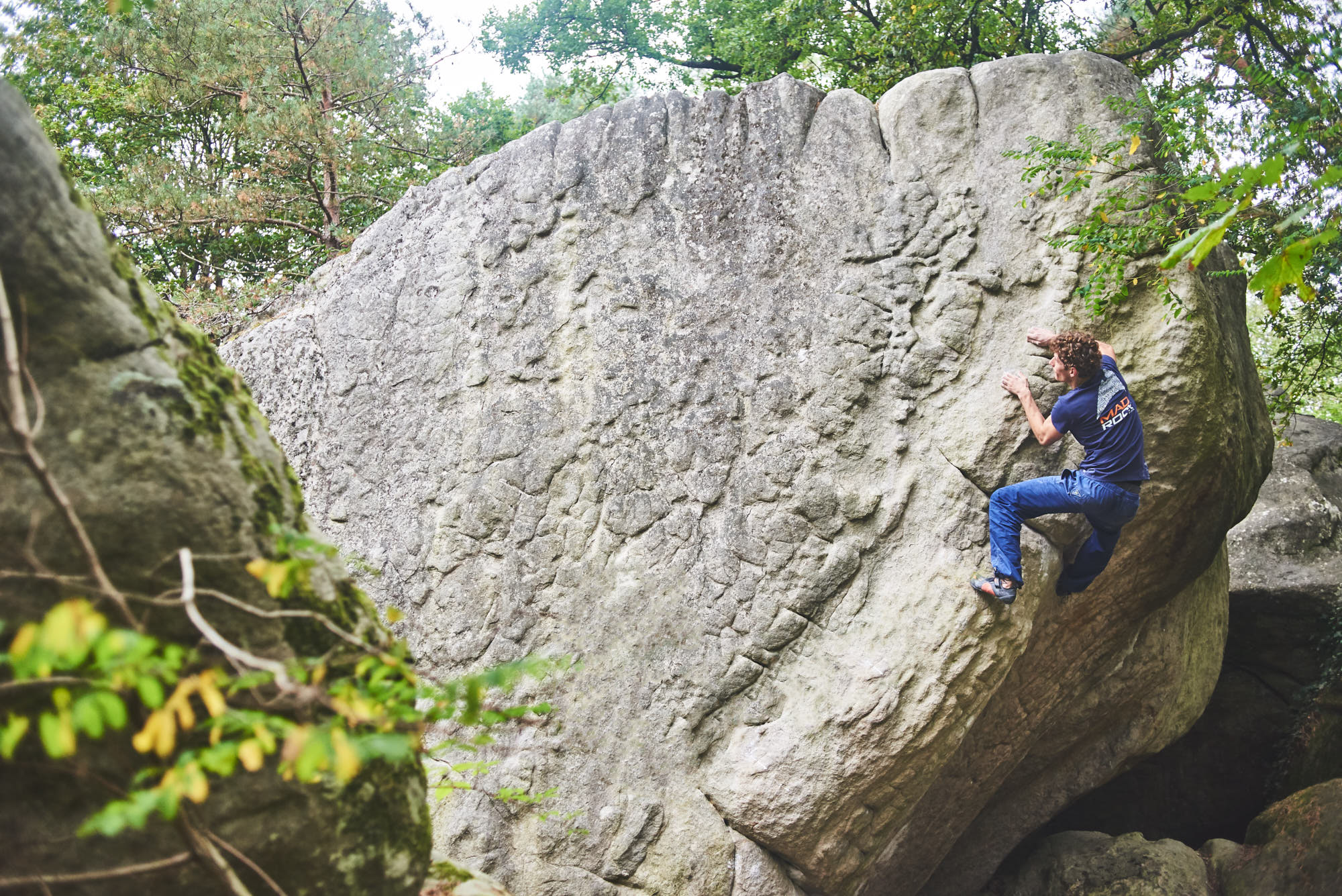 Mad Rock climber climbing a boulder problem in Fontainebleau