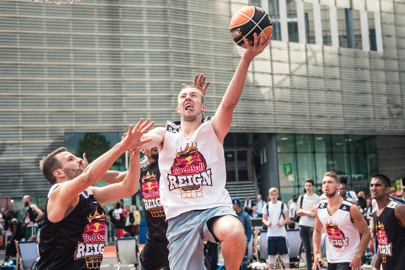 Basketball player tipping the ball up to the basket in Rotterdam