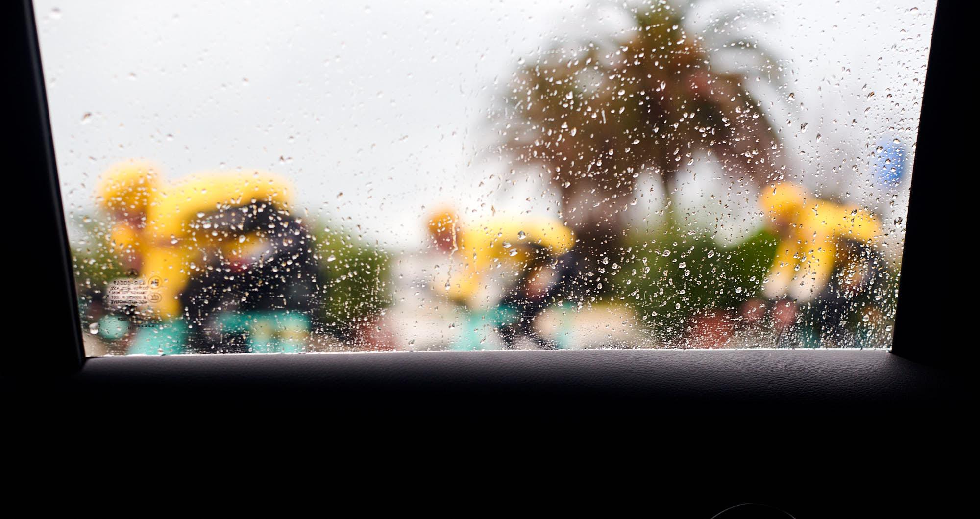Rainy car window with cyclists
