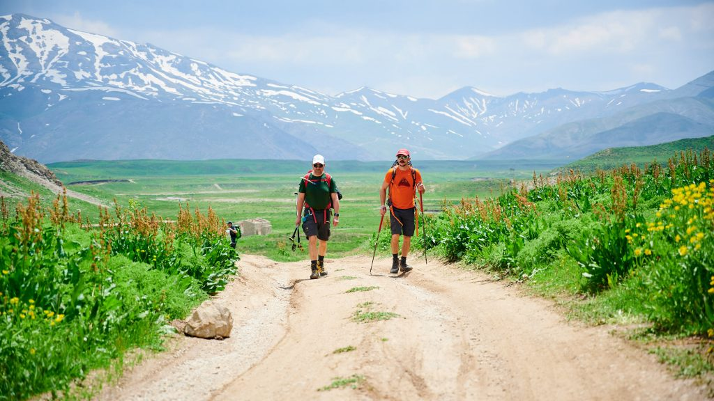 Two hikers on a gravel road in Dar valley in Iran