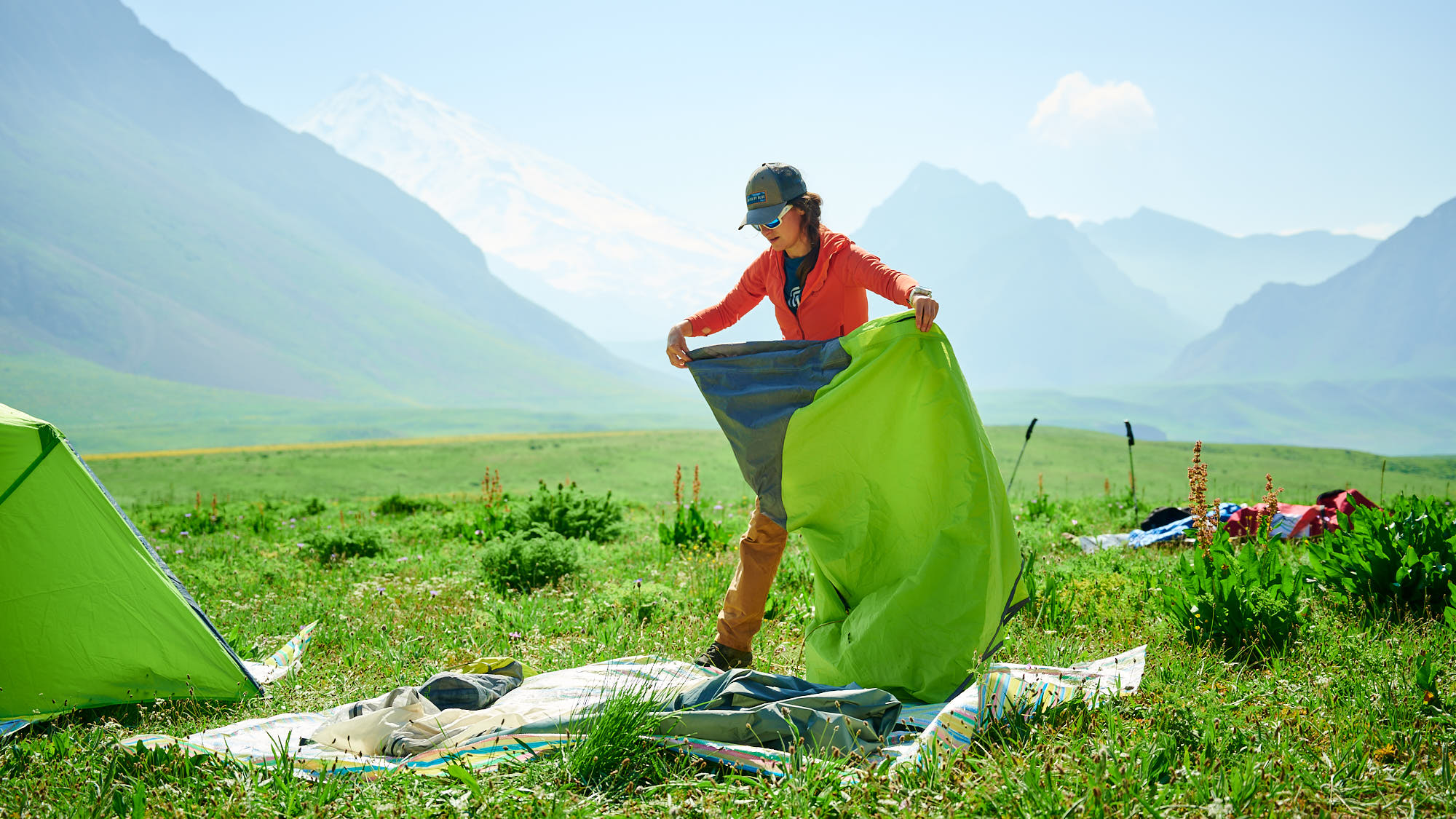 Hiker packing her tent after a night of camping in Dar valley in Iran
