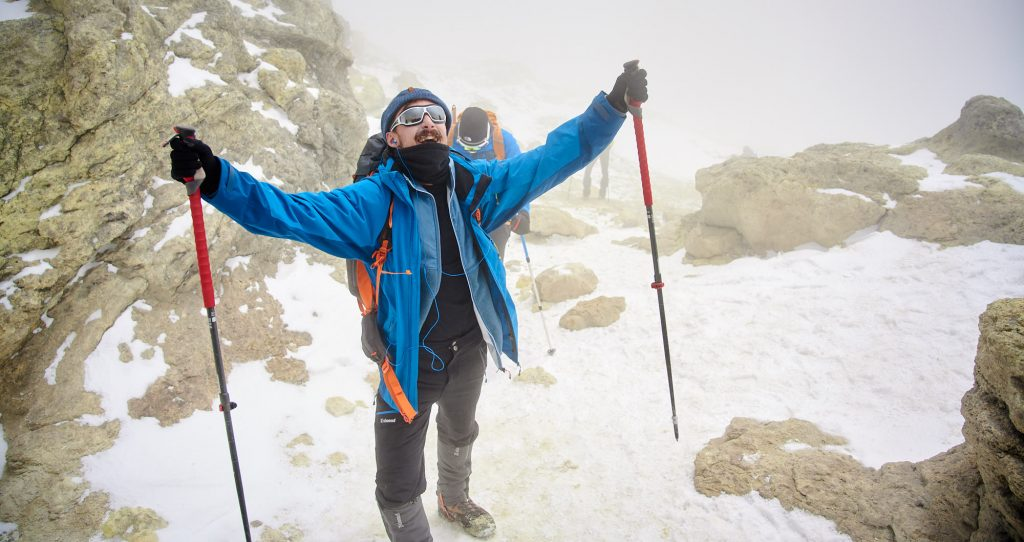 Ecstatic mountaineer on the summit of Mount Damavand in Iran