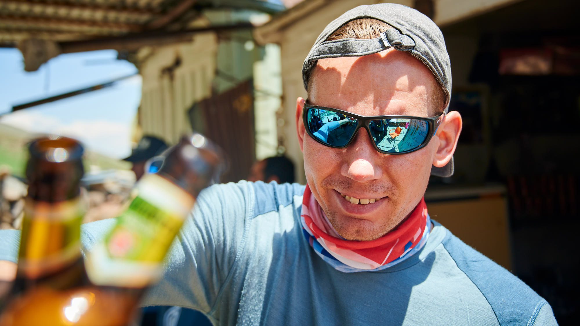 Climber celebrating a successful climb with a non-alcoholic beer in Iran