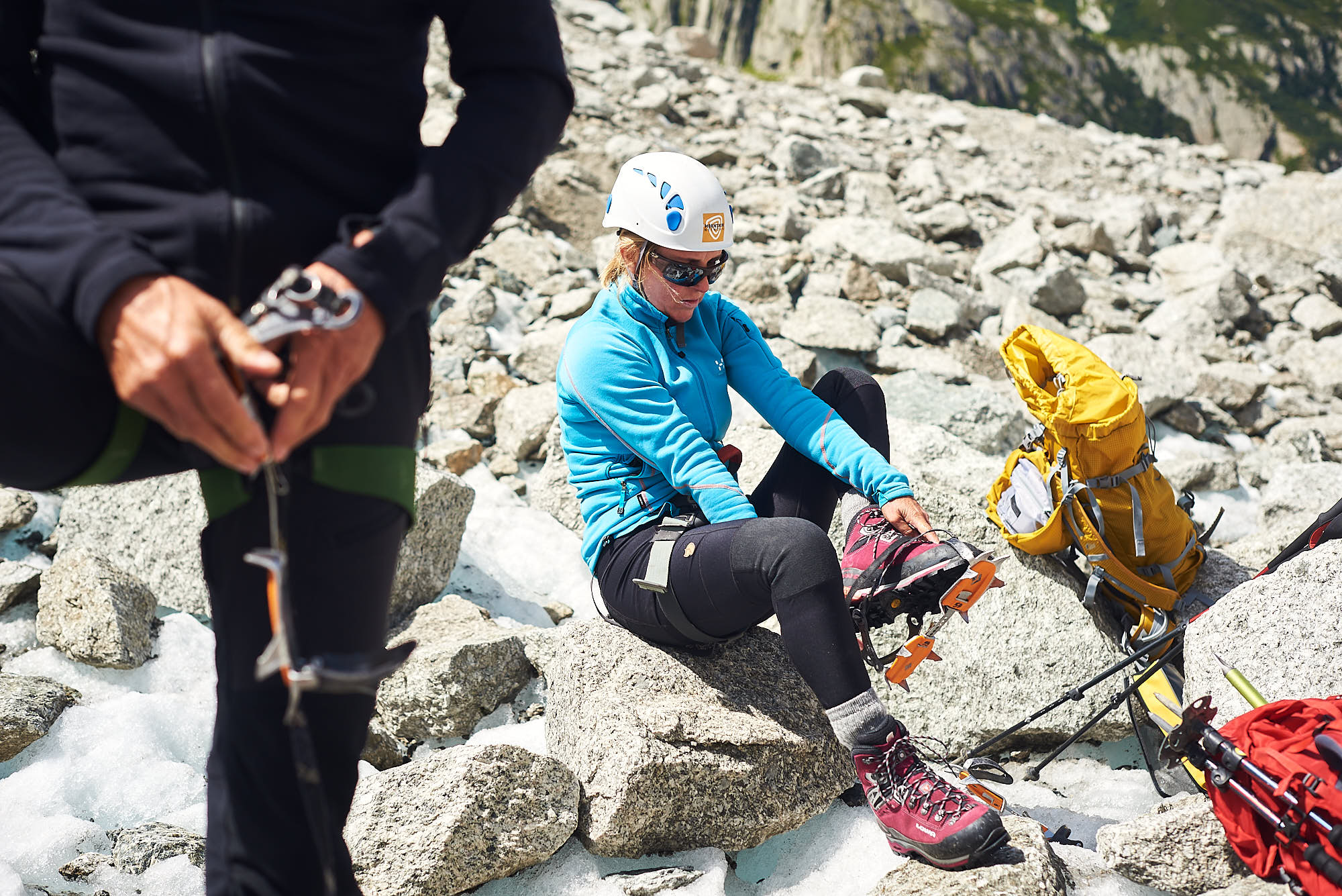 Mountaineer putting on crampons on the Mer de Glace glacier near Chamonix