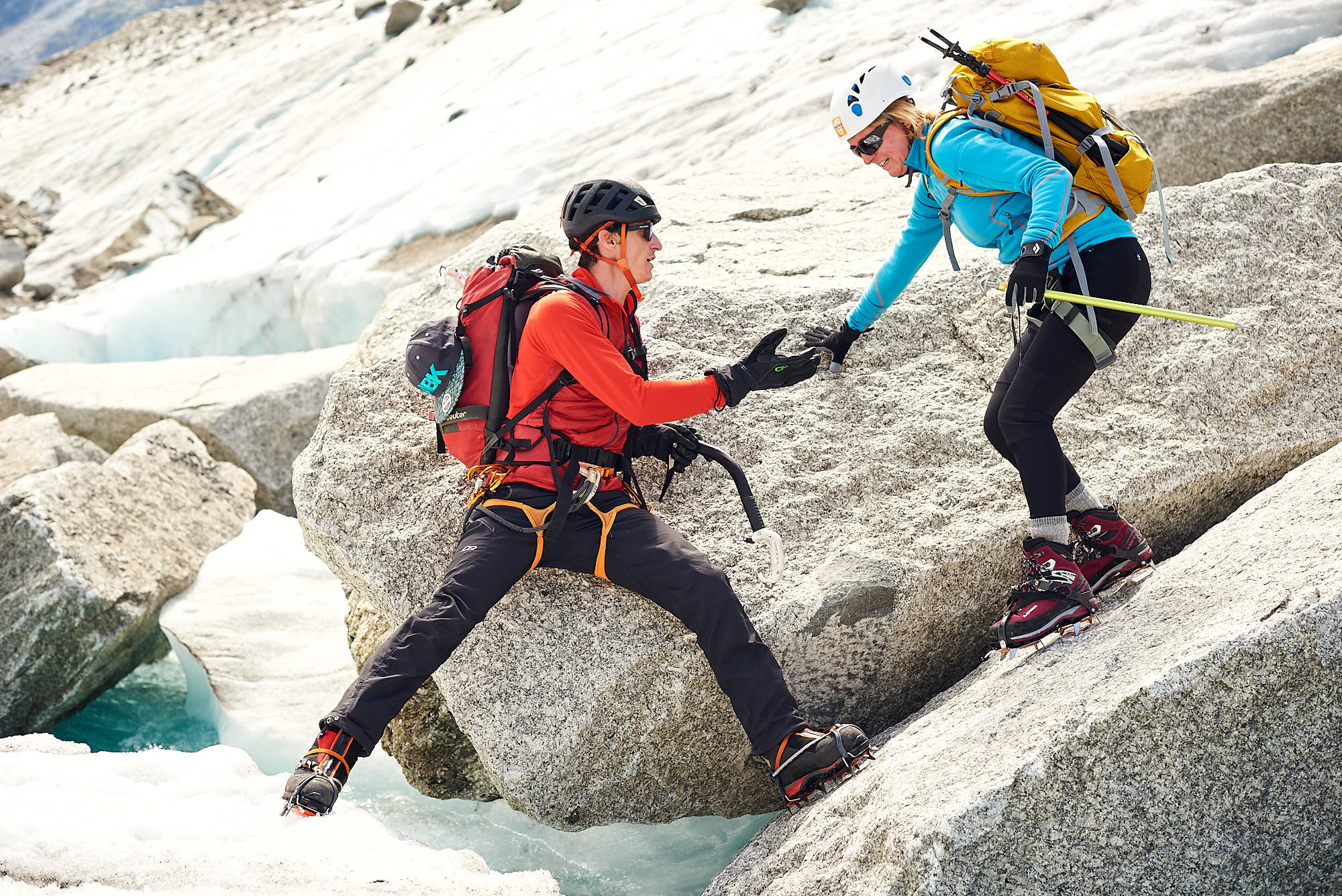 Mountain guide helping a client across a glacial stream on the Mer de Glace glacier