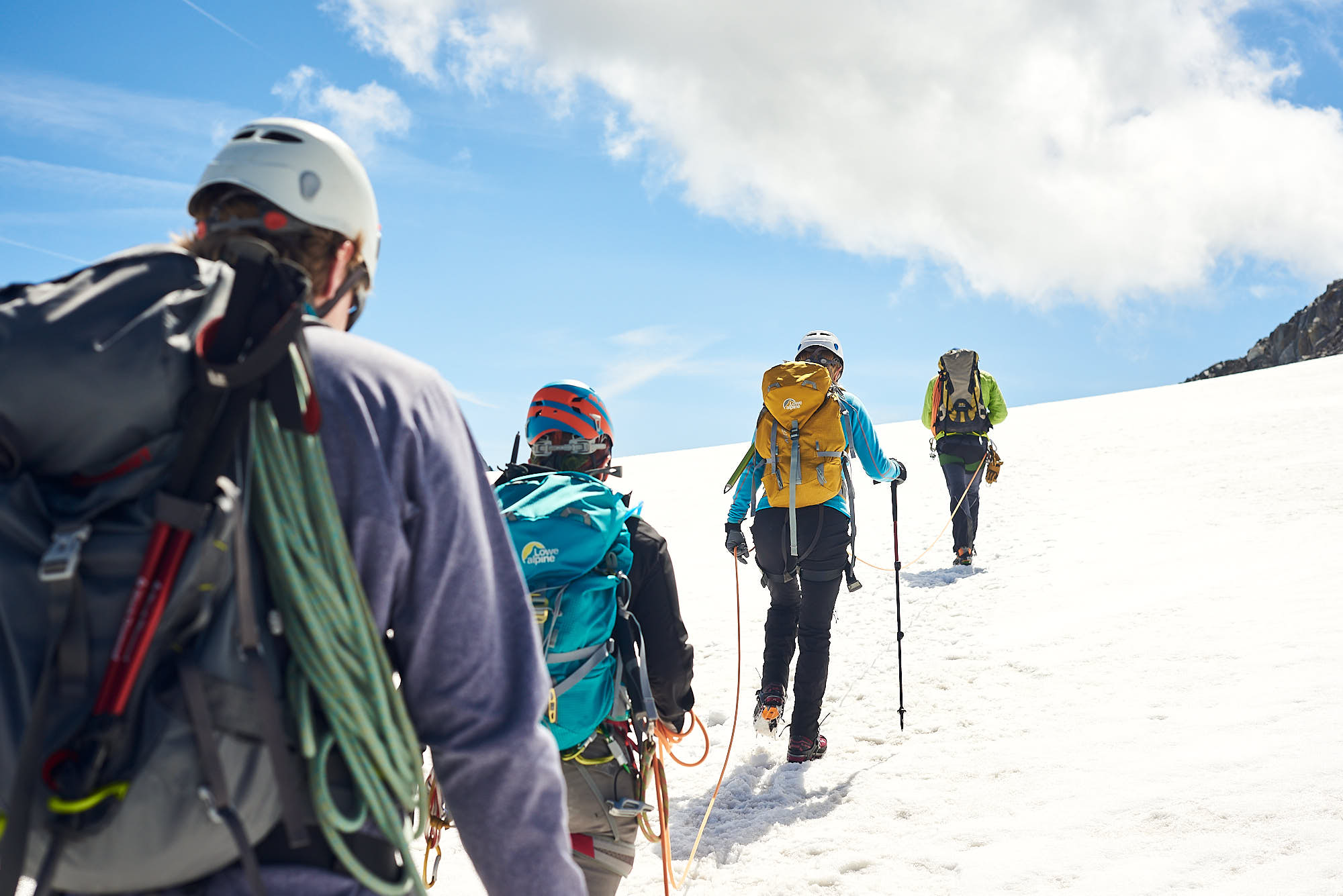Mountaineers climbing a snowy hill in the European Alps