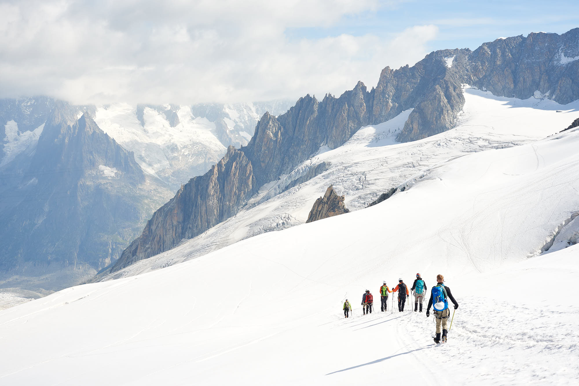Group of alpinists walking down a snow slope in the Alps
