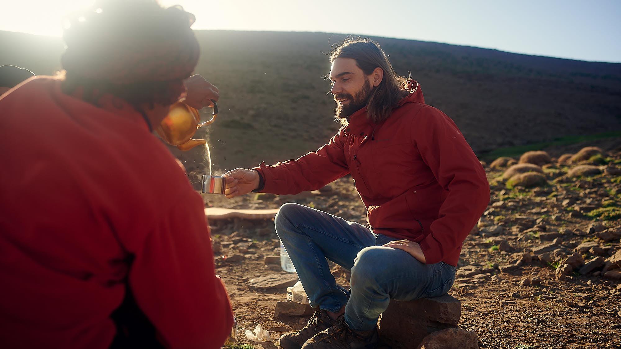 Hiker drinking tea in Morocco's High Atlas mountain ridge