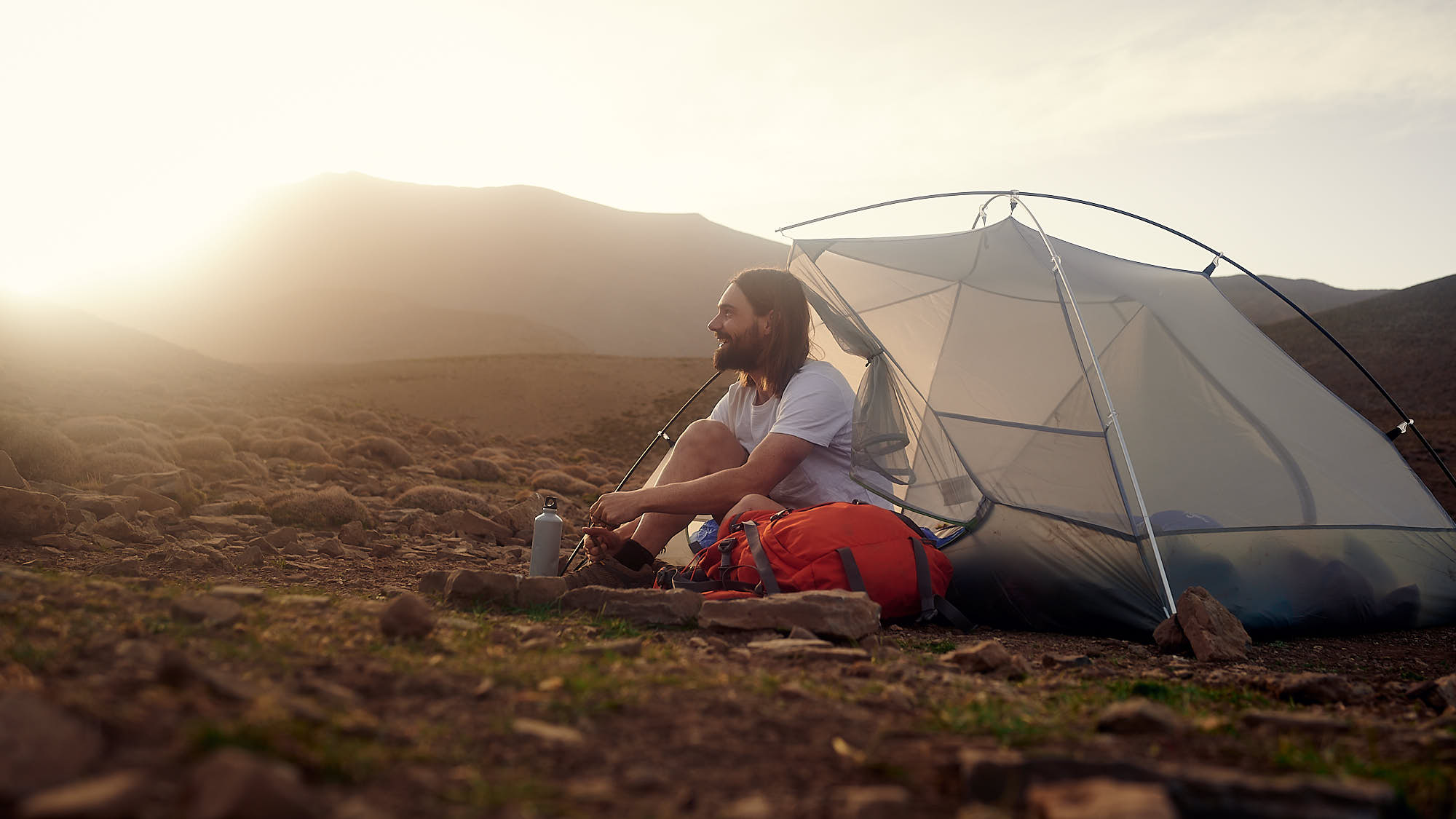 Hiker sitting by his tent in Morocco's High Atlas mountain ridge