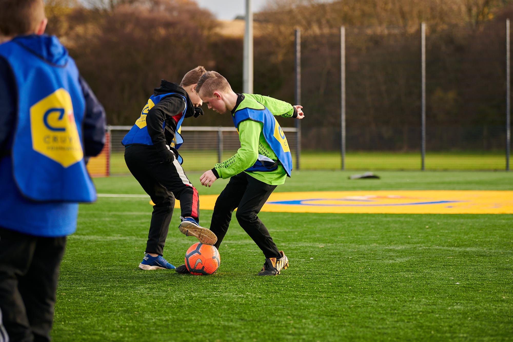 Kids playing football on a Cruyff Court