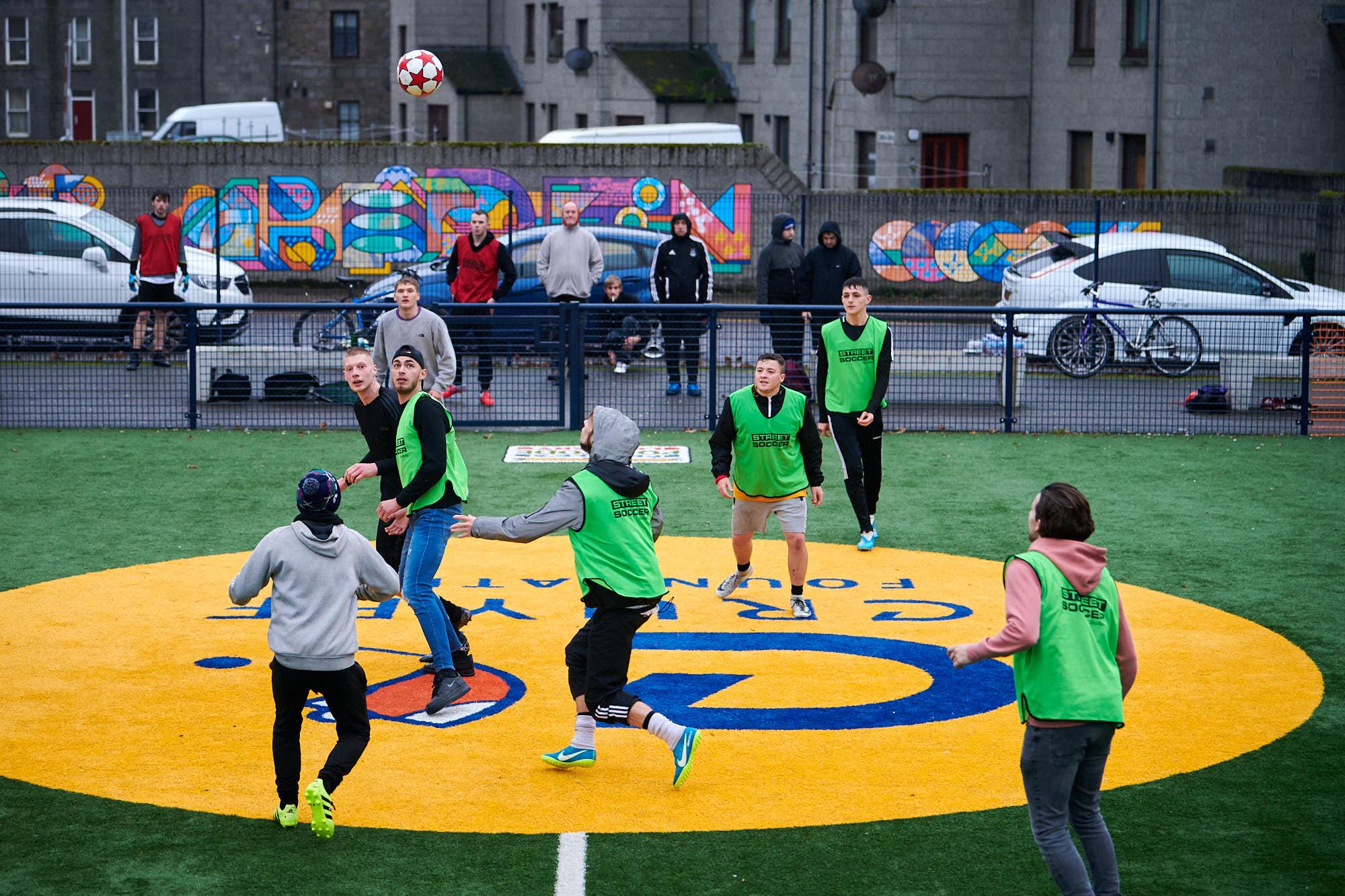 Men playing football on a Cruyff Court in Aberdeen